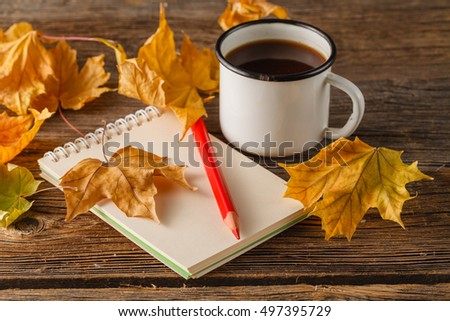 Writing-books, multi-coloured pencils in a cup and autumn leaves on a woden background. Concept for Back to school.