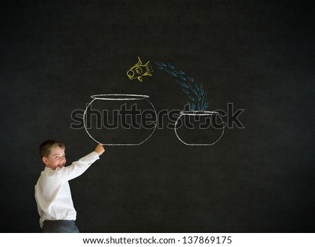 Writing boy dressed up as business man with chalk fish jumping from small bowl to big bowl on blackboard background - stock photo