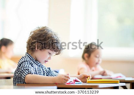 Writing boy in classroom - stock photo