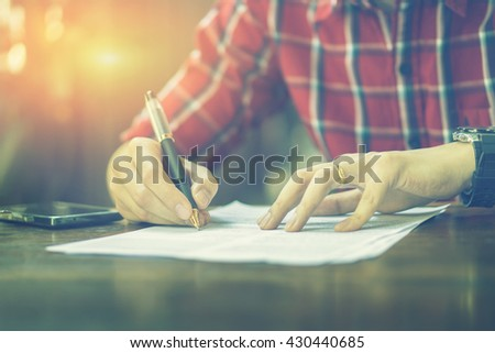 Writing,Businessperson Signing Contract,Man writing paper at the desk, man writing with pen,register a marriage,divorce,man Signing, Contract, Form in office ,vintage color ,selective focus.copy space - stock photo