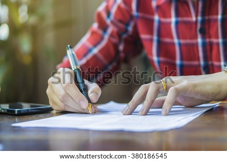 writing,Businessperson Signing Contract,man writing paper at the desk with pen and reading books,Sign Contract Form filling petition form agreement of divorce,morning light ,selective focus.copy space - stock photo