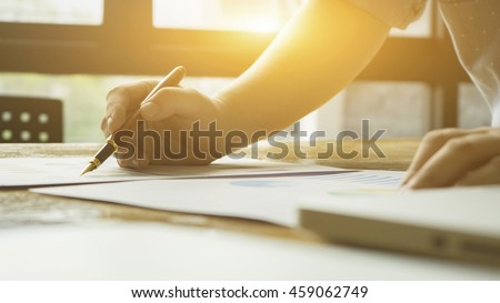 writing,Businessperson Signing Contract,man writing paper at the desk with pen and reading books,Sign Contract Form filling petition form agreement of divorce,vintage tone,selective focus  - stock photo