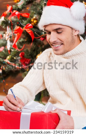 Writing Christmas letter. Handsome young man in Santa hat writing Christmas letter and smiling with Christmas Tree in the background  - stock photo