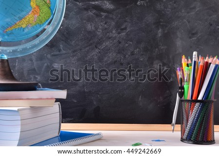 Writing desk with school tools on wood table and blackboard in the background with place in the center for title. Front view - stock photo