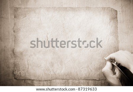 writing hand with feather on old paper parchment background - stock photo
