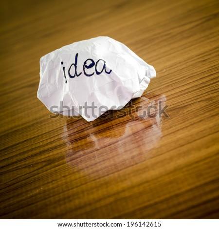 writing idea word on crumpled on wood background - stock photo