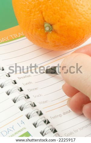 writing in a diet and nutrition journal with orange to the side - stock photo