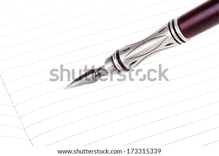 Writing in a text book with luxury retro ink pen isolated - stock photo