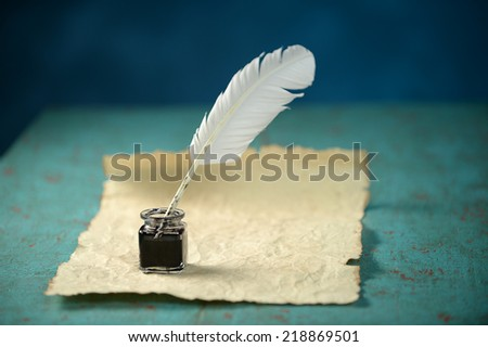 Writing Inkwell with feather and vintage paper on table - stock photo