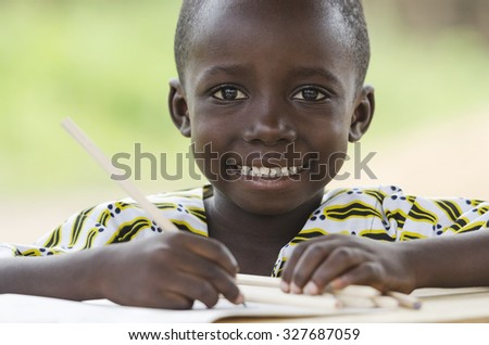 Writing little black African ethnicity boy. Handsome young African man close-up shot. Beautiful toothy smile on his face outdoors his school sitting in his desk learning his lesson. - stock photo