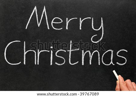 Writing Merry Christmas on a blackboard.