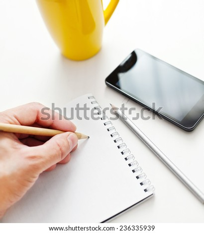 Writing notes or planning a schedule on blank spiral notebook - stock photo