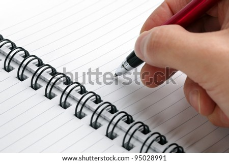 Writing notes or planning a schedule on blank spiral notebook for copy - stock photo