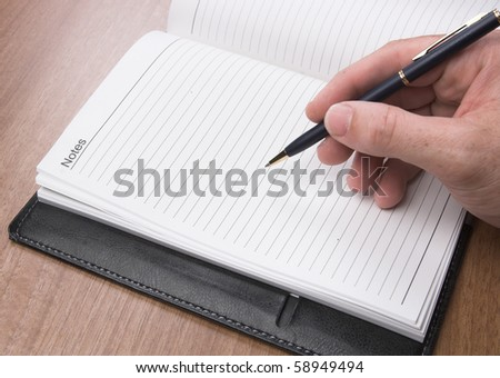 Writing on a diary - stock photo