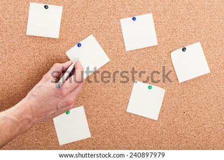 writing on sticky note on a cork board - stock photo