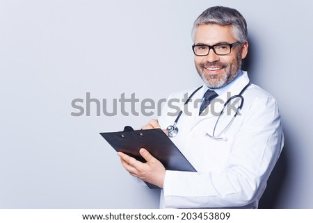 Writing prescription. Cheerful mature doctor looking at camera and smiling while writing something at his clipboard and standing against grey background - stock photo