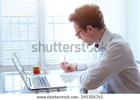 writing resume, young handsome business man working in office - stock photo