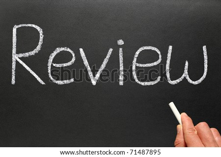 Writing review with white chalk on a blackboard. - stock photo