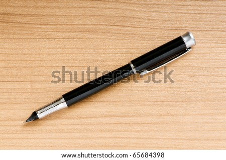 Writing silver pen on the wooden background - stock photo