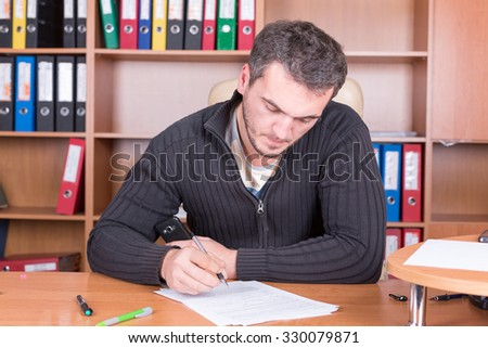 writing unshaven man in office