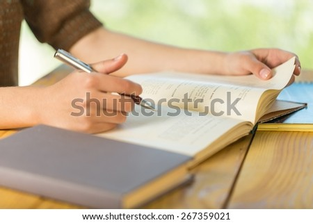 Writing. Young women and education, close up of hands of girl studying for college exam in park. Side view, copy space - stock photo