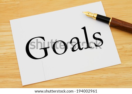 Writing your goals, A white card with text of Goals and a fountain pen on a wooden desk