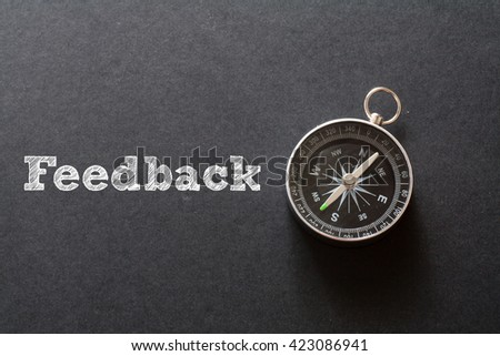 Written Feedback word on black background with compass - stock photo