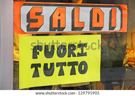 written in Italian and Balances everything out during the sale in the window of a shop - stock photo