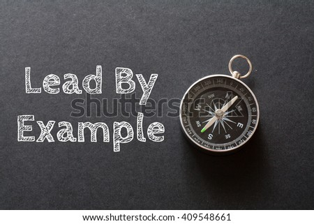 Written Lead By Example words on black background with compass - stock photo