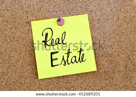 Written text Real Estate over yellow paper note pinned on cork board