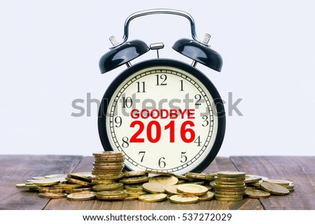 Written word Goodbye 2016 on a clock with gold coins on top of a wooden table. Financial Wealth Concept.