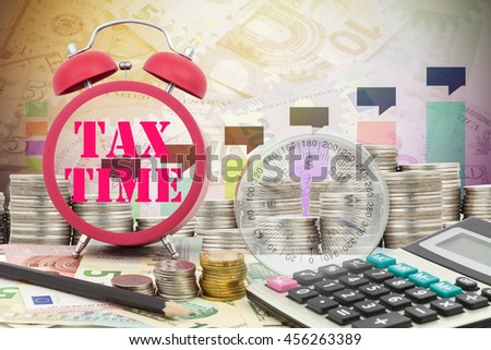 Written word Tax Time on a clock with compass ,coins and Calculator on money banknotes Euro and Dollars,concept of business planning and finance and savings - stock photo