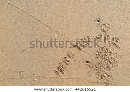 "written words ""HERE YOU ARE"" on sand of beach"