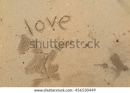 "written words ""love"" on sand of beach"