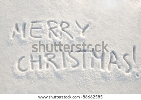Written words Merry christmas  on a snow field, new year concept - stock photo