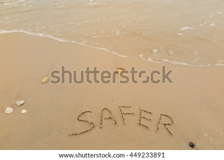 "written words ""SAFER"" on sand of beach"