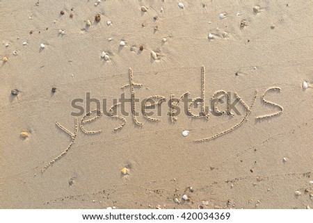 "written words ""yesterdays"" on sand of beach"