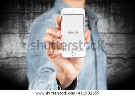 WROCLAW, POLAND - APRIL 12, 2016: Apple iPhone SE smartphone with Google logo on screen - stock photo