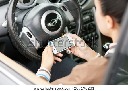 WROCLAW, POLAND - AUGUST 05, 2014: Photo of a young woman sitting in a Mini Cooper car holding an iPhone 4 smartphone device with a Google search app running - stock photo