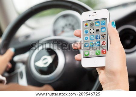 WROCLAW, POLAND - AUGUST 05, 2014: Photo of a young woman sitting in a Mini Cooper car holding an iPhone 4 smartphone device with main menu on screen - stock photo