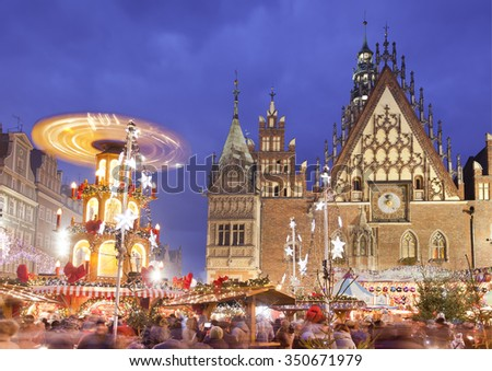 WROCLAW, POLAND - DECEMBER 12: Residents and tourists visit the Christmas market in the Old Market Square in front of City Hall on 12 December 2015 .Wroc?aw is European city of culture in 2016