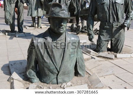WROCLAW, POLAND - JULY 06, 2015: Detail of the monument of an anonymous passerby. The monument is located in the busy section of Wroclaw the crossroads of Pilsudskiego and Swidnicka streets. - stock photo