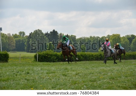 WROCLAW, POLAND - MAY 08: N.Hendzel on a horse Emar (3) and M.Mioduszewska on a horse  Bogini (8) finish in a Racecourse Partynice on May 08,2011 in Wroclaw, Poland. - stock photo