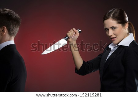 Wrong business partner. Smiling young woman in formalwear holding a knife near man in suit standing back to her - stock photo