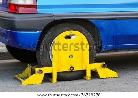 Wrong parked vehicle with yellow wheel clamp - stock photo