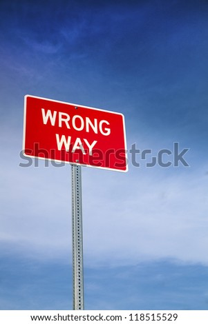 Wrong Way Road Sign and Blue Sky Behind - stock photo