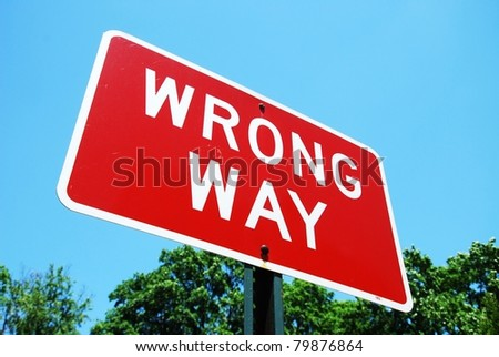 wrong way road sign on a blue sky background - stock photo