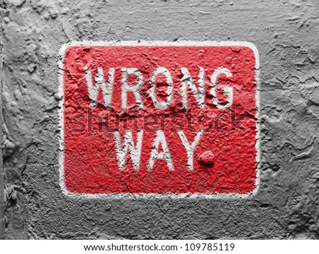 Wrong way  road sign painted on grunge wall - stock photo