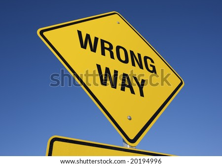 Wrong Way Yellow Road Sign against a Deep Blue Sky - stock photo