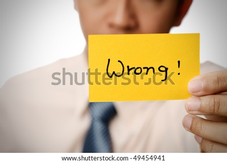 Wrong words on yellow card holding by businessman. - stock photo
